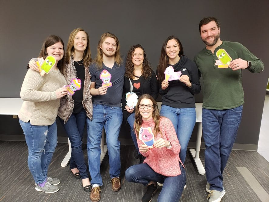 TrackFive team holding playful cupcake and popsicle cards